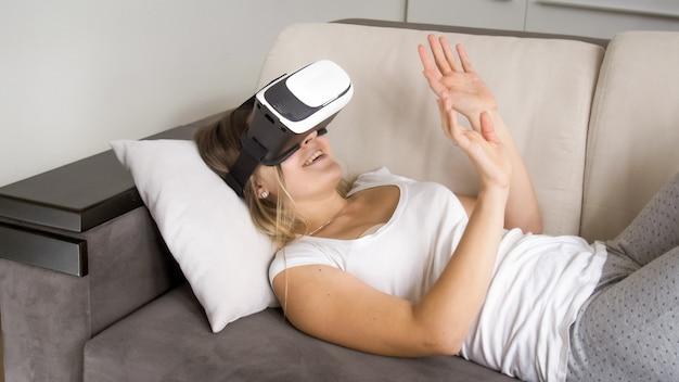 Glücklich lächelnde junge frau mit vr-brille auf dem sofa liegend und 360-grad-video ansehen