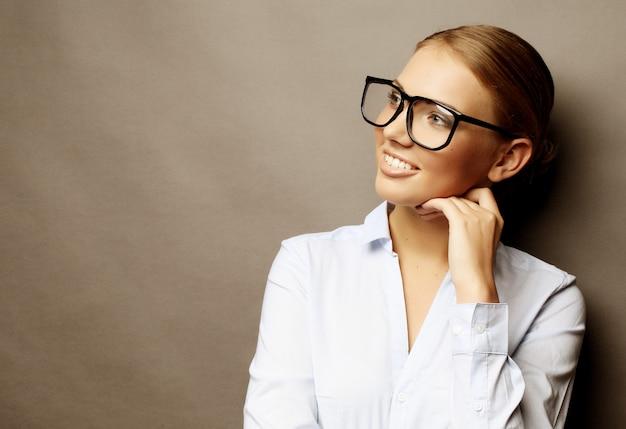 Glücklich lächelnde junge geschäftsfrau in gläsern, über grauem backgr