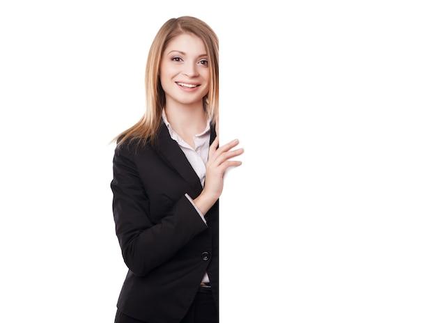 Glücklich lächelnde junge geschäftsfrau mit leerem schild, isoliert auf weißem hintergrund