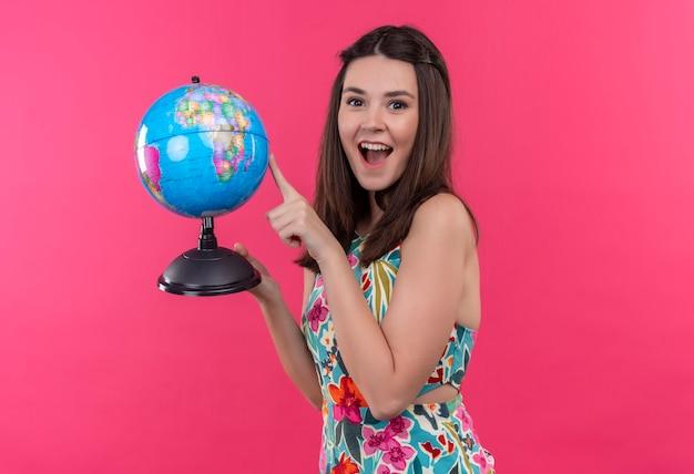 Glücklich lächelnde junge reisende frau, die erdkugel hält und mit finger auf sie auf isolierte rosa wand zeigt