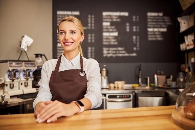 Glücklich lächelnde kellnerin, die an der fotokamera im café posiert?