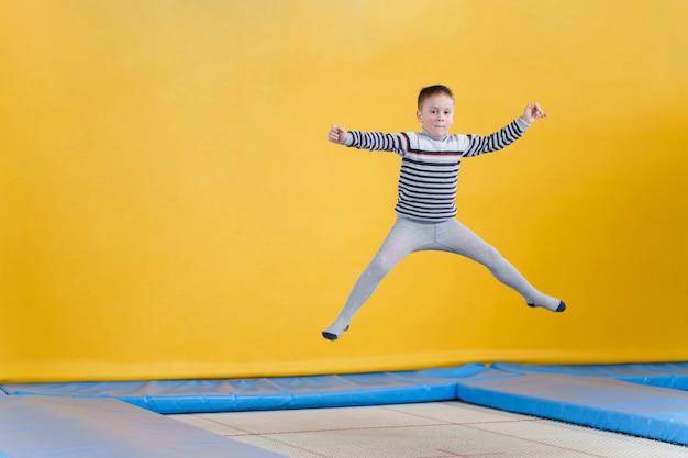 Glücklich lächelnde kleine kinder, die auf innen trampolin im unterhaltungszentrum springen