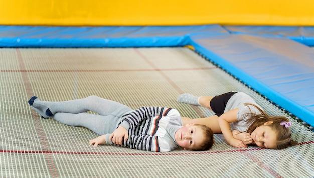 Glücklich lächelnde kleine kinder, die auf innentrampolin im unterhaltungszentrum liegen