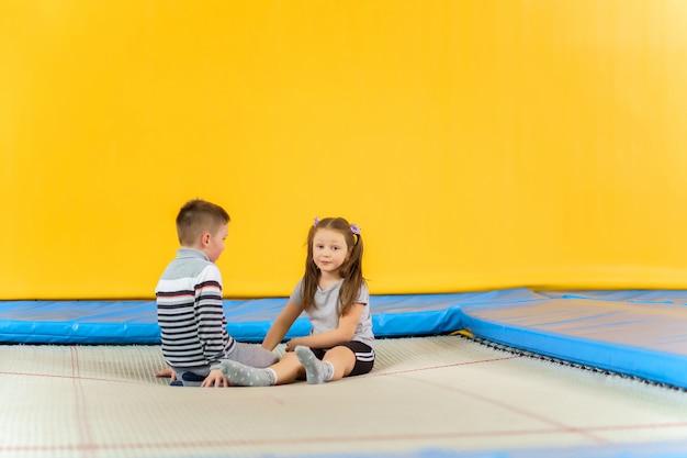 Glücklich lächelnde kleine kinder, die auf innentrampolin sitzen und im unterhaltungszentrum spielen