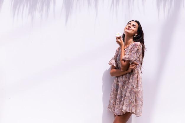 Glücklich lächelnde langhaarige frau im kleid steht auf weißer wand