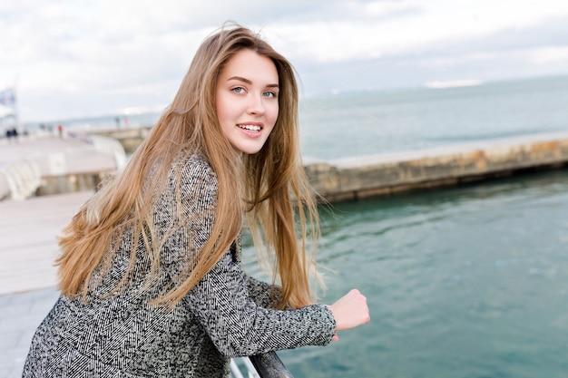 Glücklich lächelnde langhaarige frau mit großen blauen augen im roten hemd und im grauen mantel geht nahe dem meer
