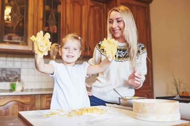 Glücklich lächelnde mutter in der küche backt kekse mit ihrer tochter.