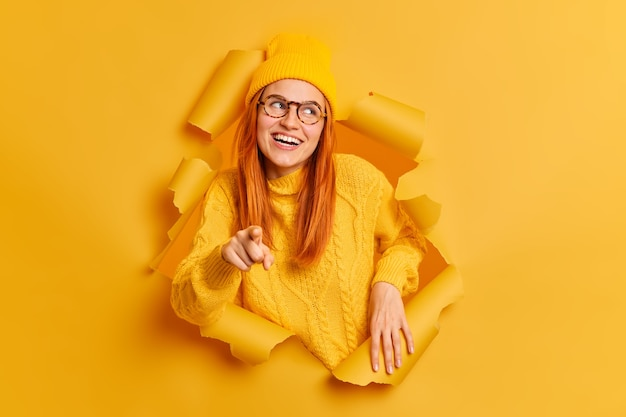 Glücklich lächelnde rothaarige frau zeigt auf, trägt hutpullover und brille.
