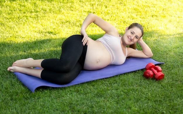 Glücklich lächelnde schwangere frau, die auf fitnessmatte im park trainiert