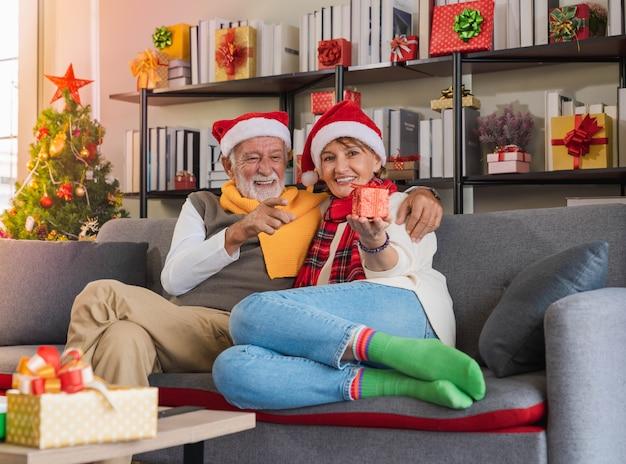 Glücklich lächelnde senior kaukasischen paar mit weihnachtsmütze sitzen zusammen auf sofa couch mit weihnachtsgeschenk zu hause mit geschmückten weihnachtsbaum im gemütlichen wohnzimmer. romantischer winterurlaub.