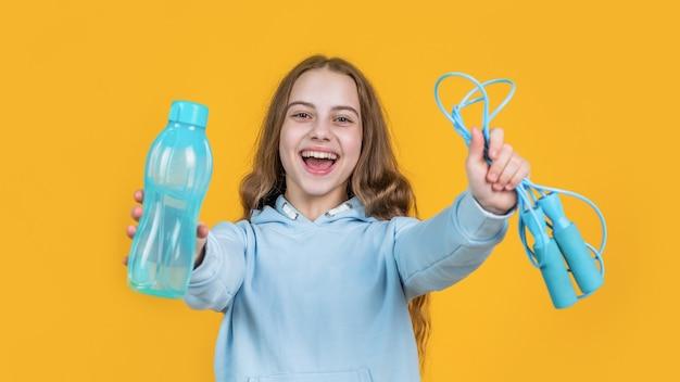 Glücklich lächelnde teenager-mädchen halten sport- oder fitnessgeräte von springseil und wasserflasche, erfrischung.