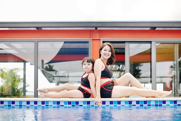 Glücklich lächelnde vietnamesische mutter und tochter in den gleichen badeanzügen, die rücken an rücken am poolrand sitzen
