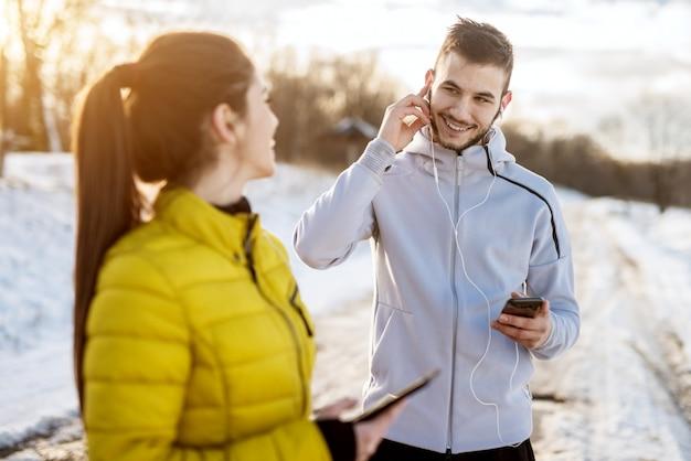Glücklich lächelnder aktiver mann in der wintersportbekleidung setzt kopfhörer auf, bevor er läuft und in ein schönes lächelndes mädchen mit einem pferdeschwanz draußen schaut