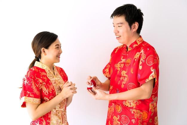 Glücklich lächelnder chinesischer mann mit rotem traditionellem cheongsam kostüm geben diamantring zu seiner freundin für verlobungsvorschlag im chinesischen neujahr 2021.