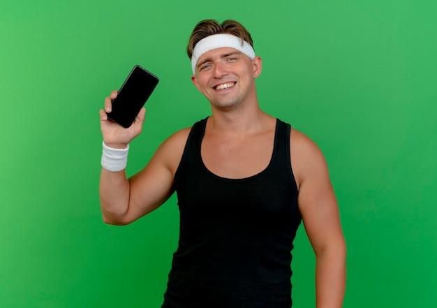 Glücklich lächelnder junger hübscher sportlicher mann, der stirnband und armbänder trägt, die handy lokalisiert auf grün zeigen