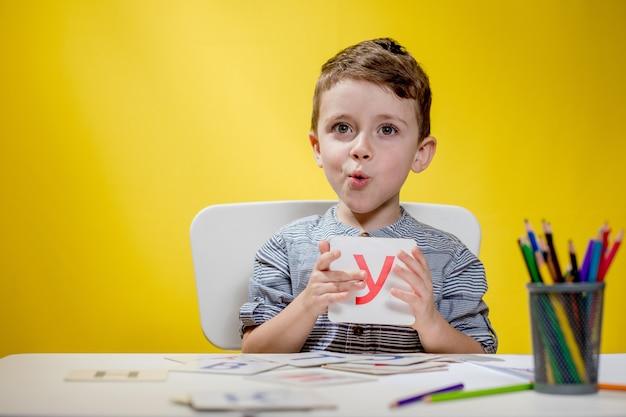 Glücklich lächelnder kleiner vorschuljunge zeigt briefe zu hause, die am morgen vor schulbeginn hausaufgaben machen. englisch lernen für kinder.