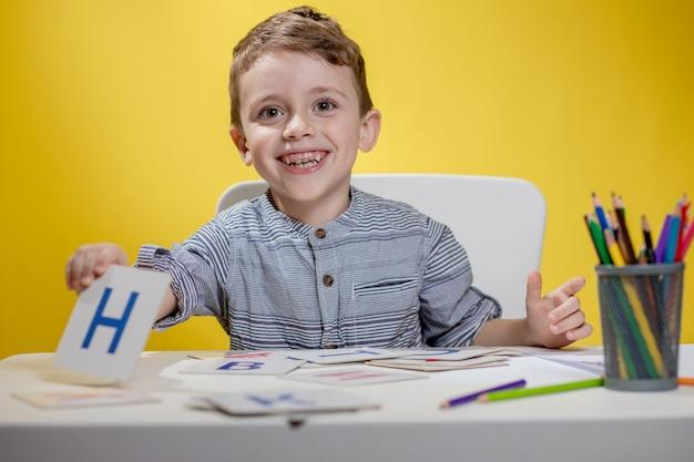 Glücklich lächelnder kleiner vorschulkind zeigt briefe zu hause, die am morgen vor schulbeginn hausaufgaben machen. englisch lernen für kinder.