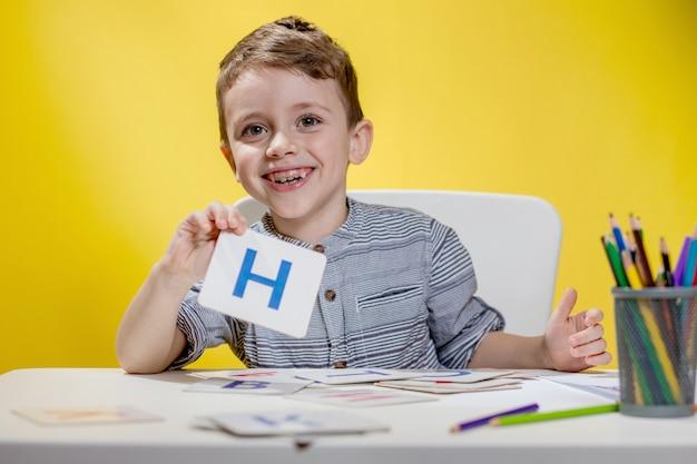 Glücklich lächelnder kleiner vorschulkind zeigt briefe zu hause, die am morgen vor schulbeginn hausaufgaben machen