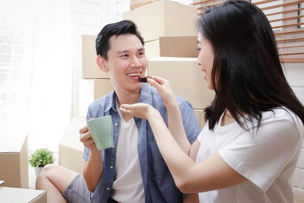 Glücklich lächelndes asiatisches paar zieht in ein neues zuhause die frau füttert ihren mann mit snacks. familienkonzept, der beginn eines neuen lebens.