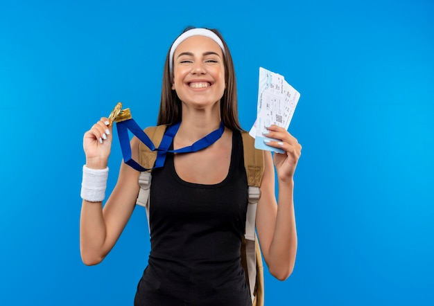 Glücklich lächelndes junges hübsches sportliches mädchen mit stirnband und armband und medaille um den hals, das medaillen und flugtickets einzeln auf blauer wand mit kopierraum hält