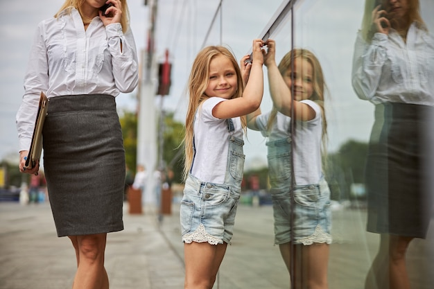 Glücklich lächelndes weibliches kind, das die fotokamera anschaut, während es in der nähe des glasgebäudes steht