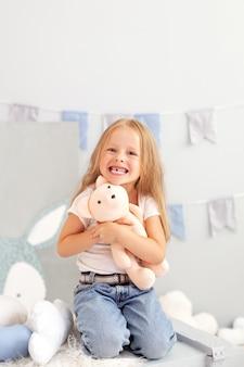 Glücklich lächelndes zahnloses kleines blondes mädchen. kind lächelt ohne seine milchzähne im kinderzimmer.
