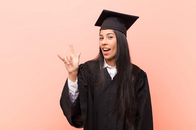 Glücklich, lustig, selbstbewusst, positiv und rebellisch sein, mit der hand rock- oder heavy-metal-zeichen machen