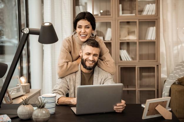 Glücklich mit gefühlen. lachende ansprechende frau, die sich auf den rücken ihres mannes stützt, während er am laptop arbeitet