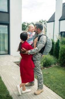 Glücklich nach dem wiedersehen. die familie fühlt sich nach dem wiedersehen wirklich glücklich, während der ehemann vom militärdienst zurückkehrt