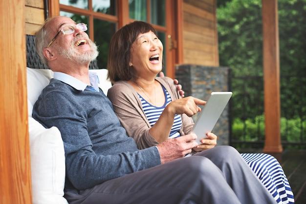 Glücklich pensionierter ehemann und ehefrau auf einem tablet