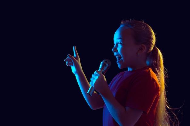 Glücklich singen. porträt des kaukasischen mädchens auf dunklem studiohintergrund im neonlicht. schönes weibliches modell mit lautsprecher. konzept der menschlichen emotionen, gesichtsausdruck, verkauf, anzeige, hobby, traum, musik.