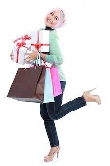 Glücklich stehende junge frau mit einkaufstasche und geschenkboxen