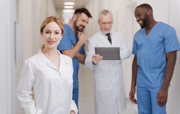 Glücklich, teil des kollektivs zu sein. schöne junge lächelnde krankenschwester, die im krankenhaus arbeitet und lächelt, während andere kollegen gadget im hintergrund verwenden