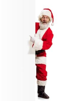 Glücklich überrascht weihnachtsmann zeigt auf leere werbewand mit kopierraum