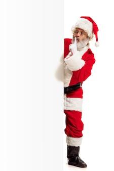 Glücklich überrascht weihnachtsmann zeigt auf leere werbewand