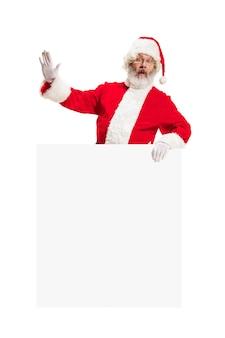 Glücklich überrascht weihnachtsmann zeigt auf leere werbung