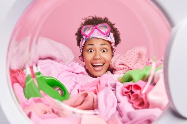 Glücklich überraschte hausfrau lädt automatische waschmaschine mit wäsche starrt auf die kamera öffnet den mund aus großem interesse trägt eine schnorchelbrille auf der stirn, die in schmutziger kleidung in der nähe von waschmittel vergraben ist