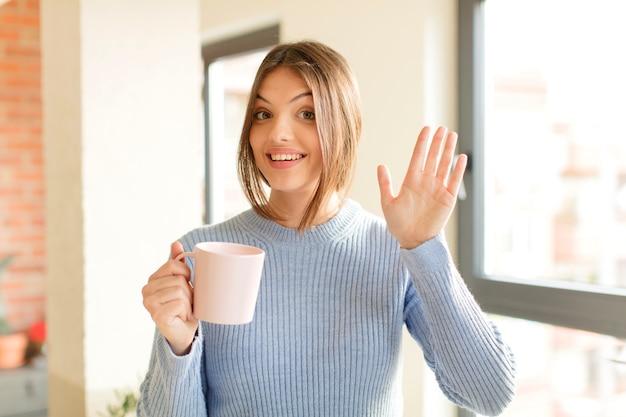 Glücklich und fröhlich lächeln, mit der hand winken, dich begrüßen und begrüßen oder auf wiedersehen sagen