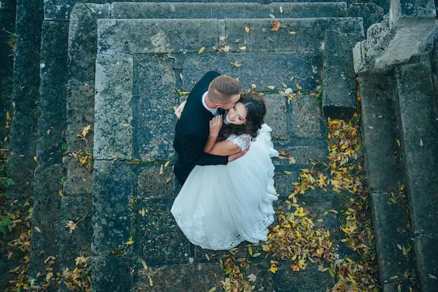 Glücklich und verliebt gehen braut und bräutigam im herbstpark an ihrem hochzeitstag
