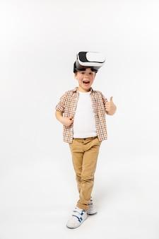 Glücklich und verwundert. kleiner junge oder kind in jeans und hemd mit virtual-reality-headset-brille lokalisiert auf weißem studiohintergrund. konzept der spitzentechnologie, videospiele, innovation.