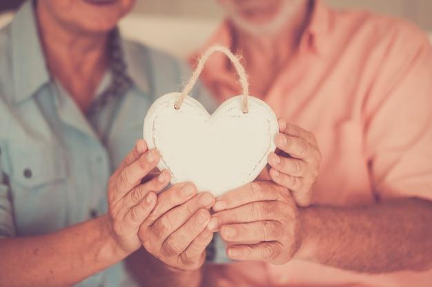 Glücklich verheiratetes älteres ehepaar, das einen handgemachten, schäbigen, schicken kamin aus weißem holz zusammenhält und ihn zeigt showing