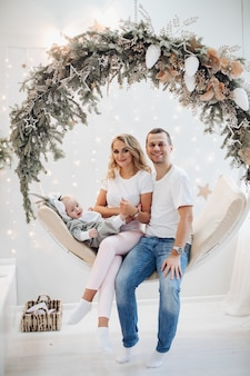 Glücklich verheiratetes paar und ihr entzückendes baby, das für weihnachtskonzeptfoto aufwirft