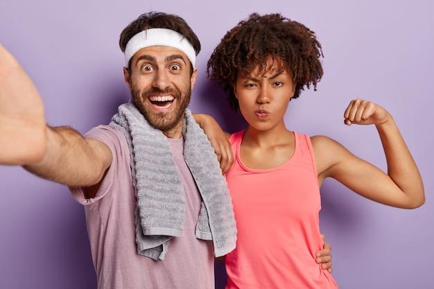 Glücklich vielfältige frau und mann machen selfie, gekleidet in freizeitkleidung, stehen eng beieinander, treiben sport