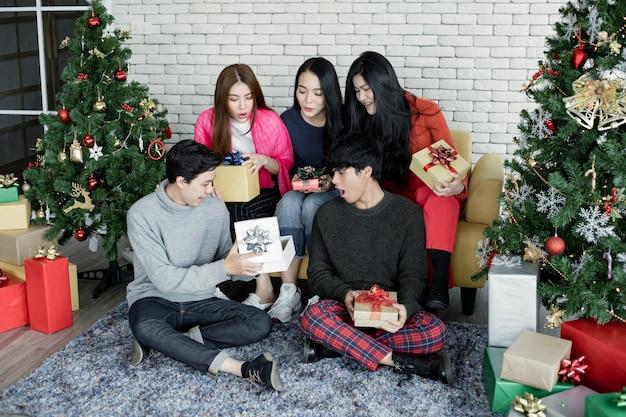 Glücklich von gruppe junger asiatischer mit geschenken zu hause beim feiern des weihnachtsfestes