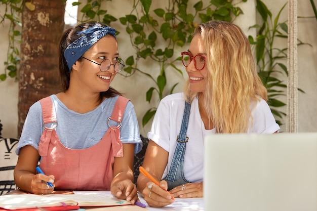 Glücklich zufrieden lächelnder teenager-student halten stifte, bereiten sich auf das schreiben von kurspapier vor