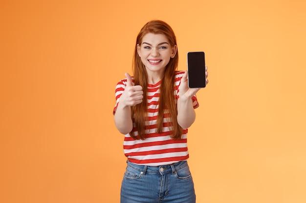 Glücklich zufriedene rothaarige attraktives mädchen jubeln show thumbup empfehlen smartphone app show mobile s ...