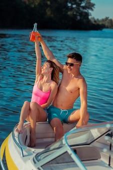 Glücklich zusammen. lächelnde junge frau mit geschlossenen augen, die sich auf ihren freund stützte, der in einem vergnügungsboot auf dem fluss sitzt