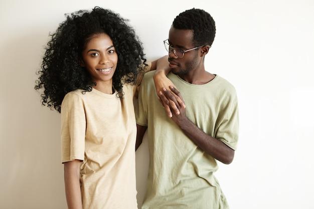Glücklich zusammen zu sein. hübscher junger afrikanischer mann, der brillen trägt, die hände zusammen mit seiner schönen freundin mit stilvollem afro-haarschnitt und zahnspangen umklammern