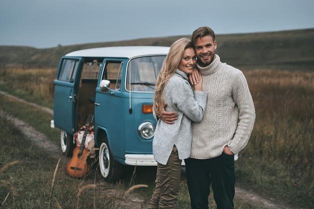 Glücklich zusammen zu sein. schönes junges paar, das umarmt und lächelt, während es nahe dem blauen retro-stil-minivan steht