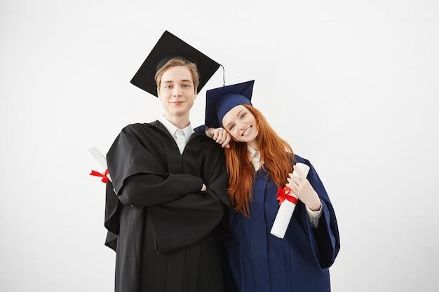 Glückliche absolventen der universität lächeln, die holsing diplome aufwerfen.